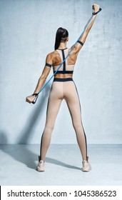 Fitness girl performs exercises for the muscles of the back and hands with resistance band. Photo of girl with beautiful athletic body on grey background. Strength and motivation.