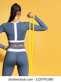 Fitness girl performs exercises for the muscles of the hands with resistance band. Photo of latin girl in fashionable sportswear on yellow background. Strength and motivation. Rear view