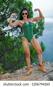 Fitness girl posing in the beach forest with a beautiful green swimsuit and sunglasses