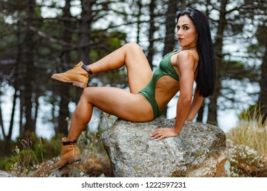Fitness girl posing on a rock in the beach forest with a beautiful green swimsuit