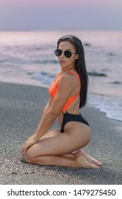 Fitness girl posing in the shore of the beach with a beautiful black and orange bikini and sunglasses
