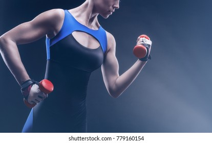 Fitness girl posing in sportswear with red dumbbells against a dark background