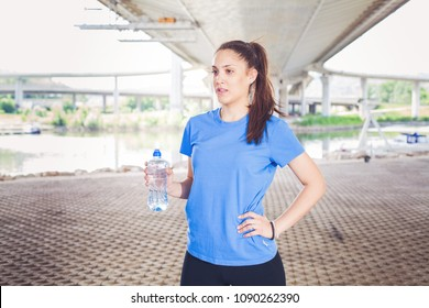 Fitness girl resting, sporty woman hold bottle of water after exercising outdoor