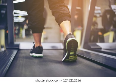 Fitness girl running on treadmill. Woman with muscular legs in gym. Fitness club with row of treadmills for fitness cardio training. Healthy lifestyle concept.selective focus