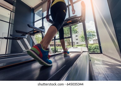 A fitness girl running on treadmill in the gym