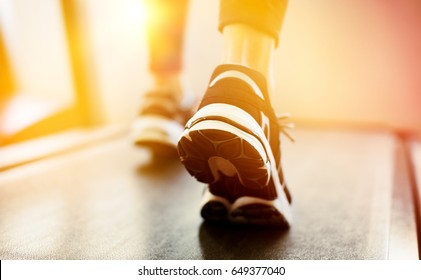 Fitness girl running on treadmill at gym. Rear view of detail of feet of young woman wearing sneakers and running on treadmill. Fitness and healthy lifestyle concept.