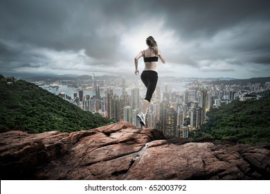 fitness girl running over hill far to the city