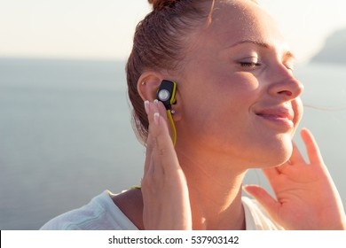 Fitness girl with sport in-ear wireless headphones - Caucasian female athlete woman wearing Bluetooth earphones