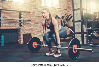 Fitness girl in sportswear doing deadlift exercise with barbell at gym