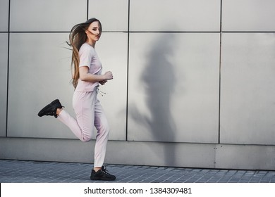 fitness girl  in sportswear working out and running along grey wall