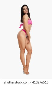fitness girl is standing sideways in a pink swimsuit isolated on white background