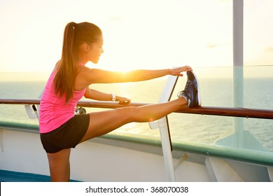 Fitness girl stretching leg on cruise vacation. Young woman adult doing stretches after running workout at sunset on balcony of a cruise ship during summer holidays. Active lifestyle.