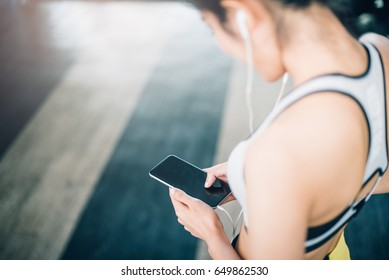 Fitness girl using her phone in the gym and listen to music