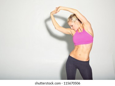 Fitness girl warming up with stretches. Isolated on white with copy space left.