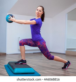 Fitness girl, wearing in sneakers posing on step board with ball