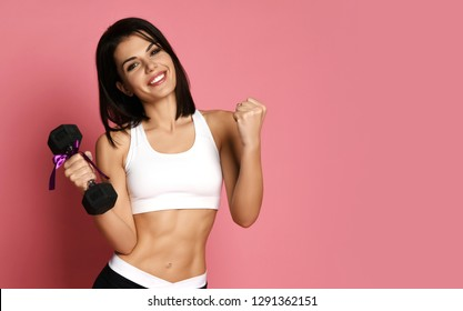 Fitness Girl working out with big weight dumbbell happy smiling on pink background. New spring sport work out concept for woman day 8 march.