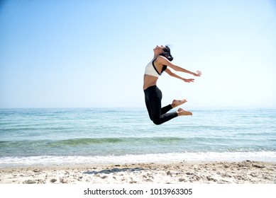 Fitness Girl working out on the beach making exercise.