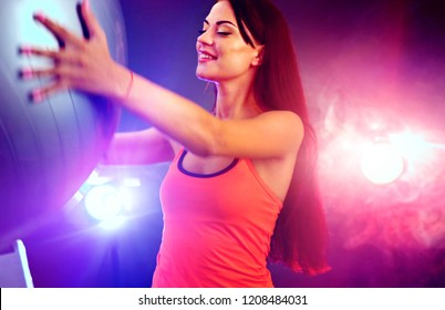 Fitness girl yoga exercising in gym with ball. Happy woman with fitball works in multi-colored rays of sport room with lens flare. Neon flash light background.