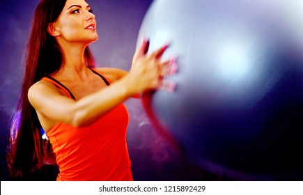 Fitness girl yoga exercising in gym with ball. Woman with fitball works for good posture in multi-colored rays of sport room. Portrait in profile with lens flare. Flash light background.