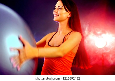Fitness girl yoga exercising in gym with ball. Happy woman with fitball works for thin waist in multi-colored rays of sport room with lens flare. Neon flash light background.