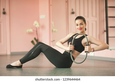 Fitness girl. Young sporty woman with perfect body having a training with pilates ring indoors in the gym