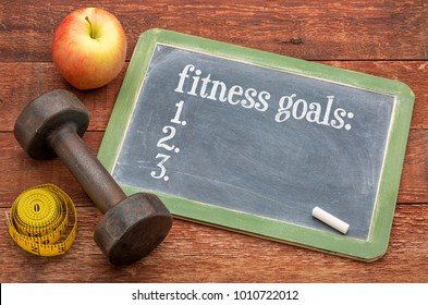 fitness goals list  -  slate blackboard sign against weathered red painted barn wood with a dumbbell, apple and tape measure