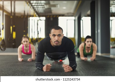 Fitness group doing plank workout training with coach indoors. Young men and women making exercise at gym. Healthy lifestyle, gymnastics concept, copy space