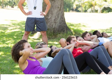 Fitness group doing sit ups in park with coach on a sunny day