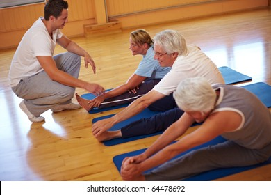 Fitness group stretching in a gym with trainer