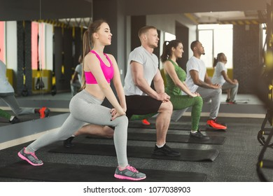 Fitness group warmup stretching training at indoors. Young men and women making aerobics exercise at gym, copy space