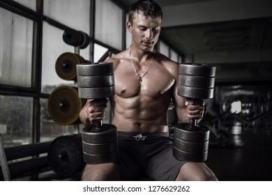 Fitness guy holding huge dumbbells in old rusty gym. Shallow depth of field
