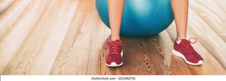 Fitness gym background panoramic banner with copy space on floor. Closeup of running shoes of fitness woman working out on exercise ball in gym center. Sport and health panorama crop.