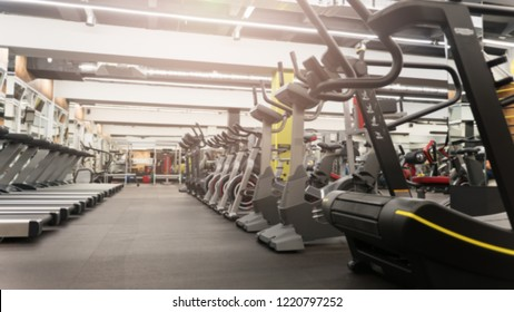 Fitness gym club with row of treadmills and elliptical trainers for fitness cardio training. Healthy lifestyle concept. Modern gym interior with equipment.