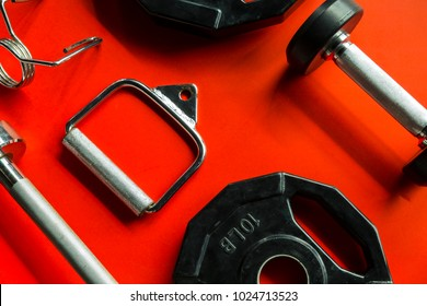 Fitness Gym concept with sports equipment on red background.
