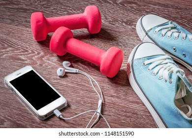 Fitness gym equipment. Sneakers, dumbbells with phone. Workout footwear. Sport trainers and music headphones.