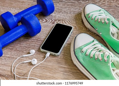 Fitness gym equipment. Sneakers, dumbbells with phone. Workout footwear. Sport gym fitness trainers and music headphones.