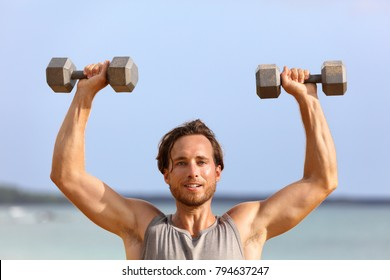 Fitness gym man lifting dumbbell weights. Male athlete with muscular arms with dumbbells overhead doing shoulder press training biceps. Athlete holding two free heavy weights.