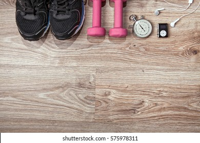 Fitness gym and running equipment. Dumbbells and running shoes, analog stopwatch and music player. Time for fitness and run. Sport accessories on the wooden floor.