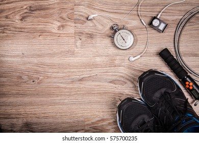 Fitness gym and running equipment. Stopwatch and running shoes, jumping rope and music player. Time for fitness. Sport running accessories on the wooden floor.
