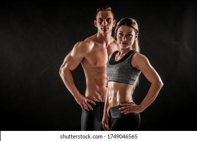 Fitness im Fitnessraum, Sport und gesundes Lifestyle-Konzept. Einige athletische Männer und Frauen zeigen ihre geübten Körper auf dunklem Hintergrund. Zwei Bodybuilder Modelle stehen und zeigen enge Muskeln.