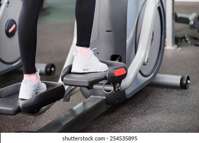 Fitness gym workout. Cropped image of young beautiful woman in sports clothing doing exercises in the gym on elliptical cross trainer