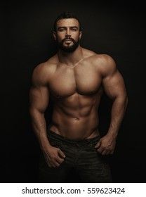 Fitness handsome and shirtless man standing on black background