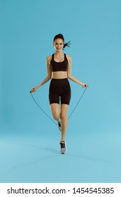Fitness. Happy woman exercising with jumping rope on blue background. Full length shot of smiling girl model with fit body doing cardio workout with skipping rope at studio