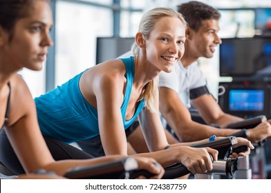 Fitness happy woman on stationary bicycle doing spinning at gym. Fit young woman working out on bike. Smiling girl exercising with group of people and looking at camera.