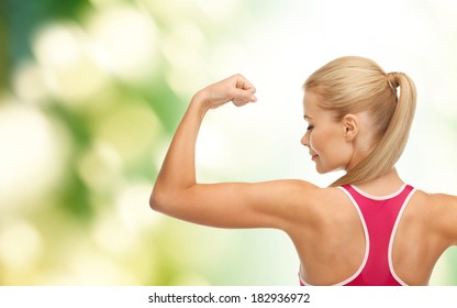 fitness and healtcare concept - young sporty woman showing her biceps