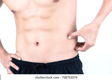 Fitness and health concept. Fit sport man touching his waist and measuring his body fat amount, isolated on white background. Half naked Asian chinese lean muscular male wearing a black shorts.
