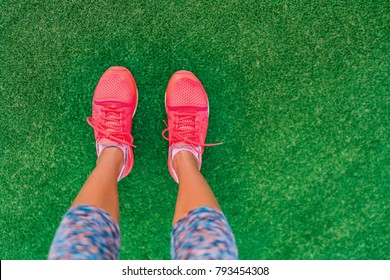 Fitness and health concept. Top view of running shoes woman standing on grass pov selfie of feet during exercise run workout outdoors. Sport and active lifestyle.
