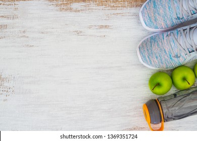 Fitness and healthy active lifestyle background concept.  Training sneakers,  water bottle and green apples on grunge white wooden background. Top view with space for your text.