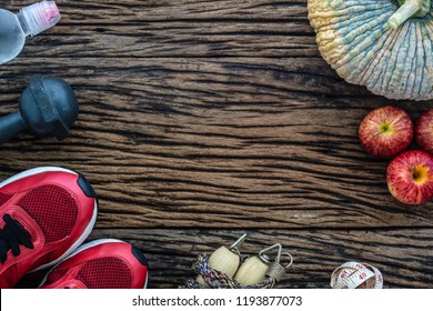 Fitness, healthy and active lifestyles Concept, Top view image of red sport shoes, jumping rope, dumbbell, pumpkin and red apples aligned on  grunge wood floor