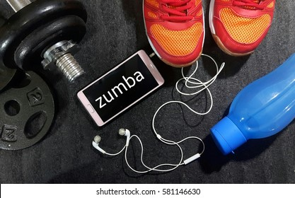 Fitness, healthy and active lifestyles concept. Dumbbells, sport shoes, smart phone with earphone and water bottle gym floor with word zumba